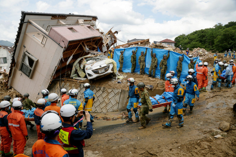 Image: Rescue workers carry the body of a victim killed by a landslide following heavy rains in Kumano, Japan