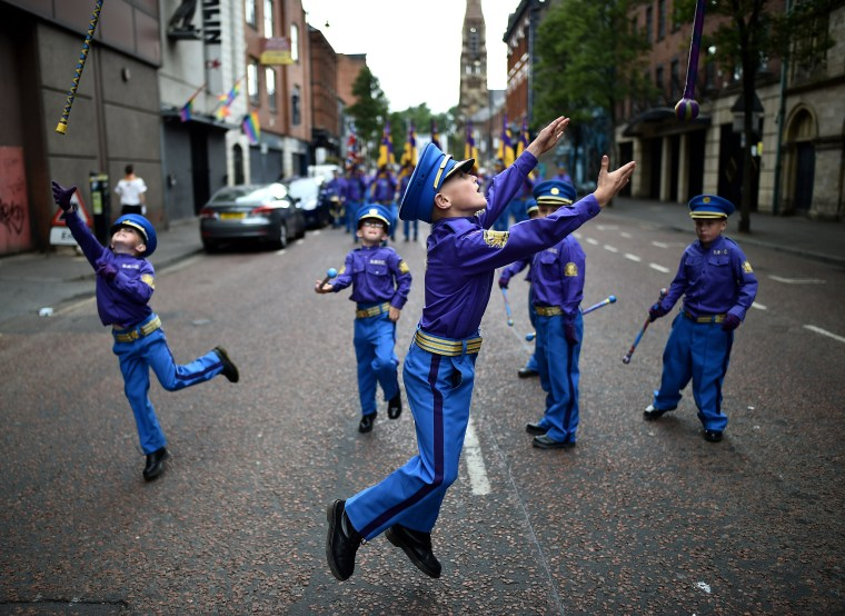 Image: Young band members throw their batons in the air