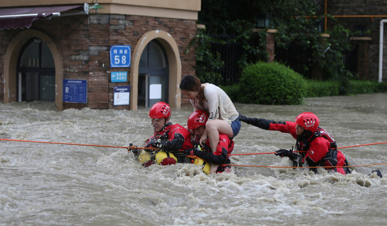 Image: Firefighters rescue a stranded woman on a flooded street, following heavy rainfall in Chengdu