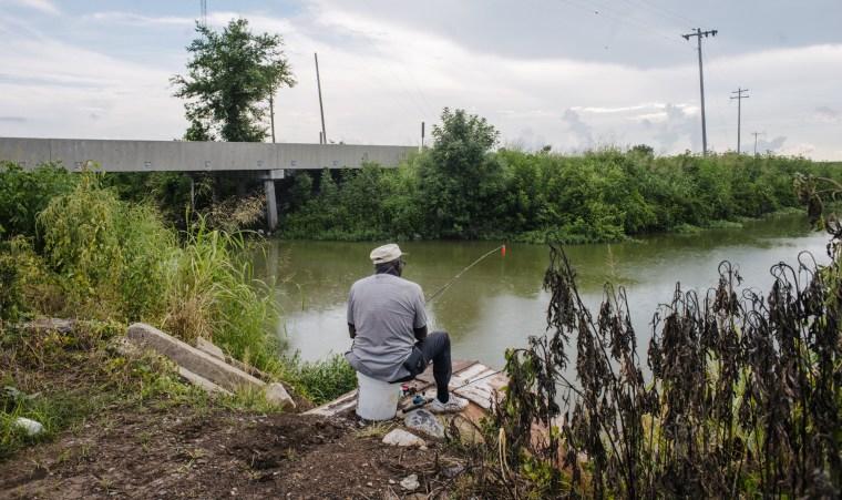 Image: A man fishes alongside a rebuilt bridge on a waterway in Washington County near Greenville