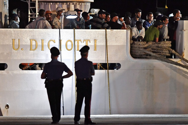 "Image: People wait to disembark from the Italian Coast Guard vessel ""Diciotti"" at the port of Pozzallo, Sicily"