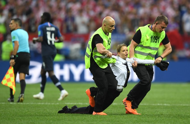 Image: A pitch invader is taken away by the security during the 2018 FIFA World Cup Final between France and Croatia