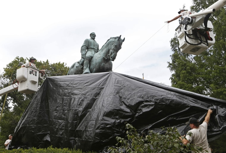 Image: City workers drape a tarp over the statue of Confederate General Robert E. Lee in Emancipation park in Charlottesville, Virginia, on Aug. 23, 2017.