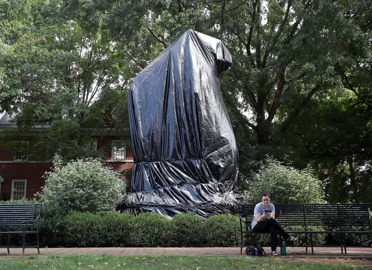 """Image: The statue of Thomas Jonathan \""""Stonewall\"""" Jackson stands covered by a black tarp"""