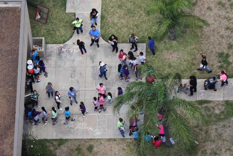 Image: Migrant children make their way inside a building at Casa Presidente in Brownsville