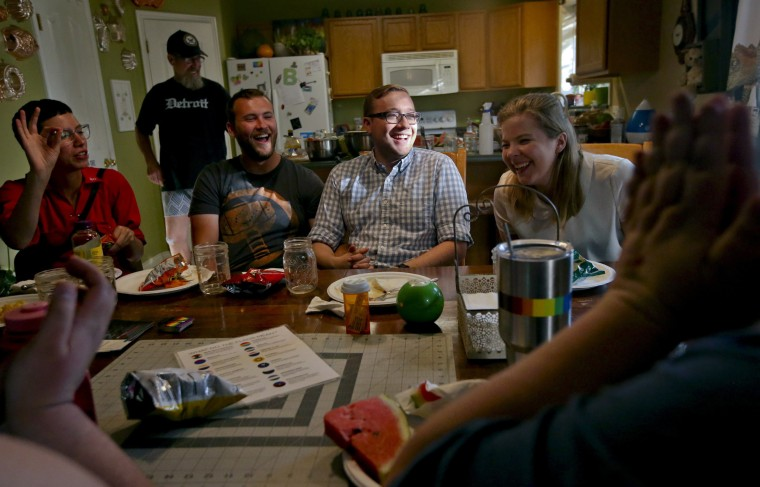 Taylor Steed, center, of Orem, and Nick Maughan, center left, of Provo, at a QueerMeals gathering