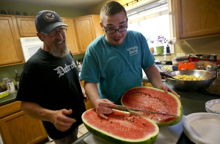 Cameron Raps, right, reacts after cutting open a watermelon beside Jeff Pool during a QueerMeals gathering