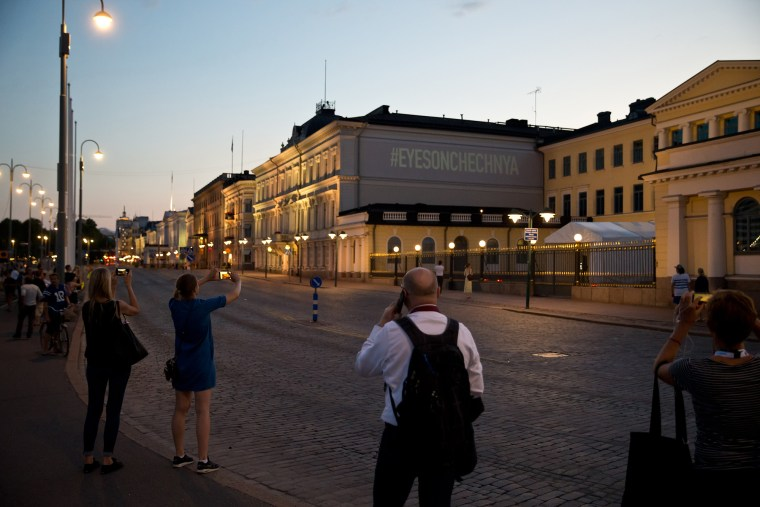 Image: People take pictures of a screen projected sign next to the president's castle in Helsinki