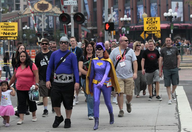 Image: People wearing costumes walk during the Comic Con International convention in San Diego