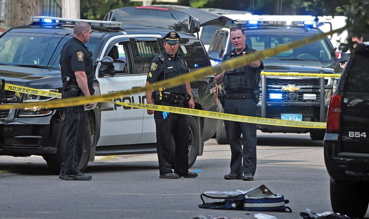 Image: Officers work at the scene where a Weymouth police officer was shot