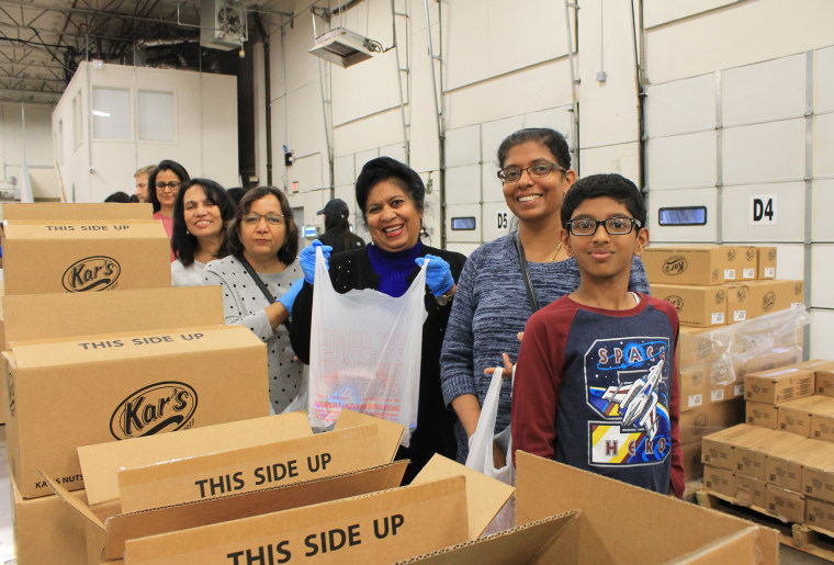 Image: Members of the Indian American Council volunteer to sort and pack food items