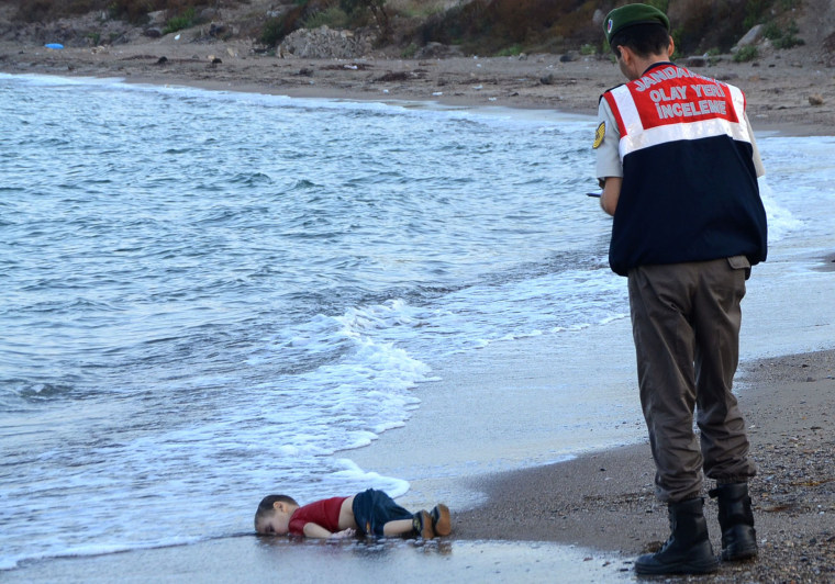 Image: A Turkish police officer stands next to the body of Aylan Kurdi in 2015