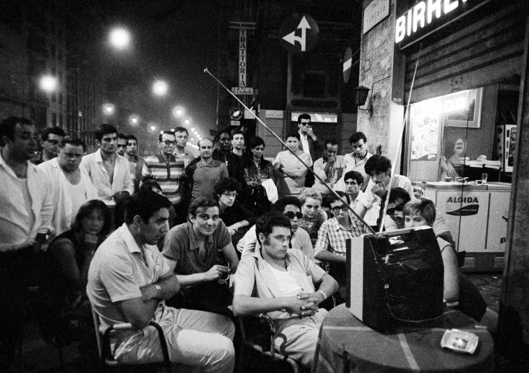 Italians watch the moon landing at a sidewalk cafe in the center of Milan.