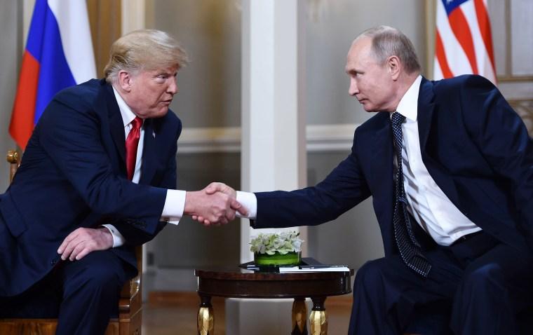 Image: President Donald Trump and Russian leader Vladimir Putin shake hands before a meeting in Helsinki