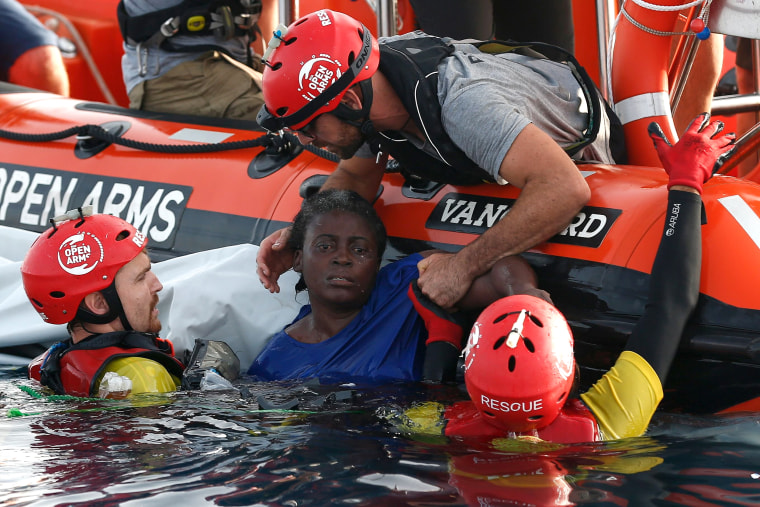 Image: Members of the Spanish NGO Proactiva Open Arms rescue a woman in the Mediterranean
