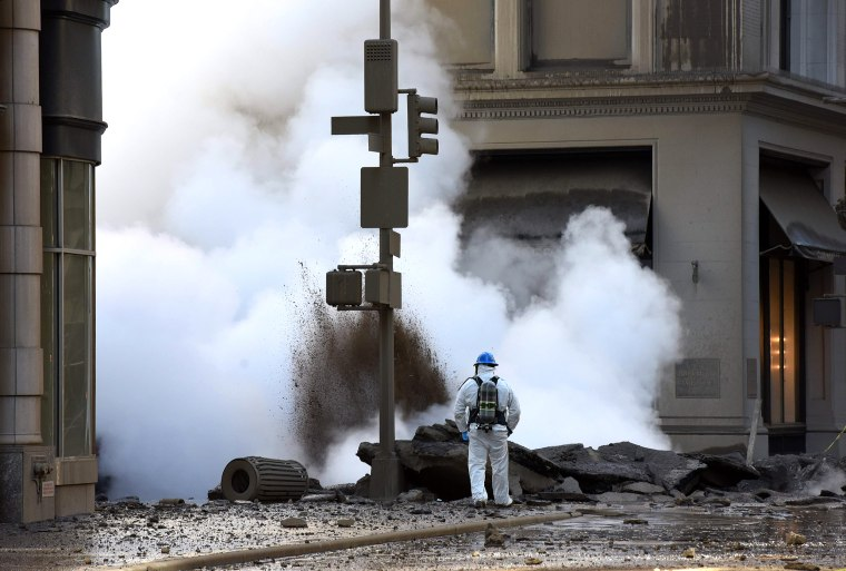 Image: A worker looks at steam coming from 5th Avenue after a steam explosion tore apart the street