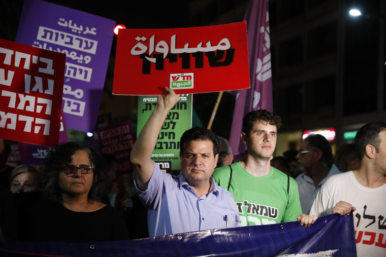 "Image: Knesset Member Ayman Odeh holds a sign reading ""Equality"""