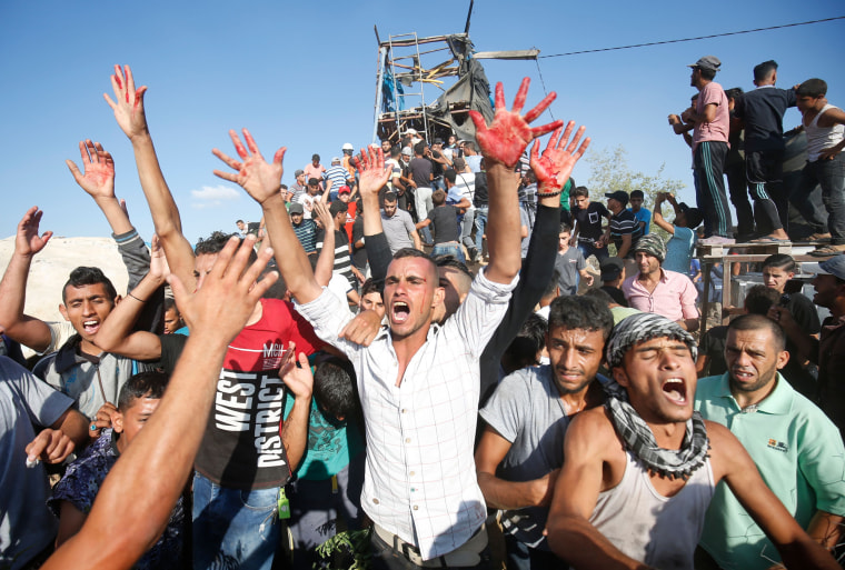 Image: Palestinians react with bloodied hands outside a Hamas outpost that was struck by Israeli bombardment near Khan Yunis in the southern Gaza Strip