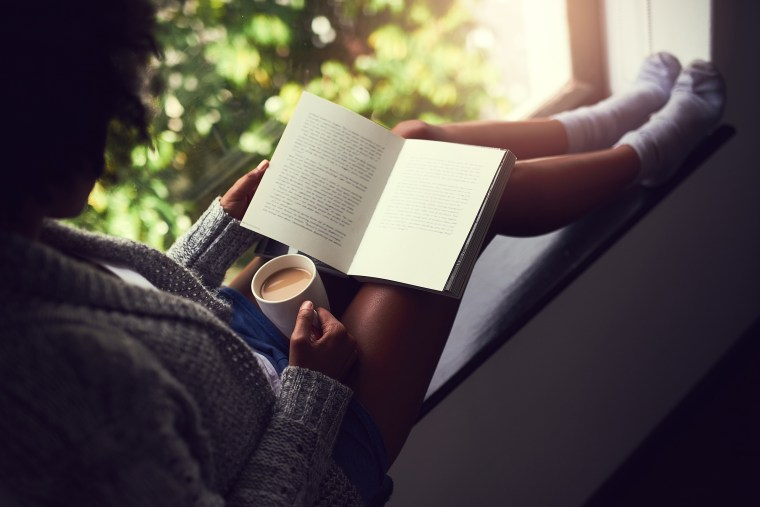 Image: young woman reading a book while enjoying a cup of coffee at home