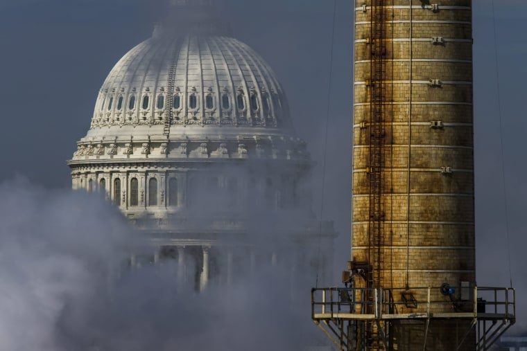 Image: The dome of the U.S. Capitol is seen behind the emissions, and a smokestack, from the Capitol Power Plant, which stopped burning coal under a 2013 reform plan.