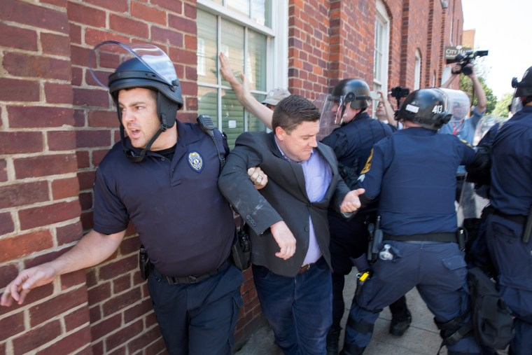 Image: Police escort Jason Kessler, organizer of the 'Unite the Right' rally, as he is rushed away after a press conference at City Hall in Charlottesville, Virginia, Aug. 13, 2017.