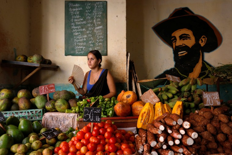 Image: A woman sells vegetables and fruits next to the portrait of the late Cuban revolutionary Camilo Cienfuegos at the local market in Havana