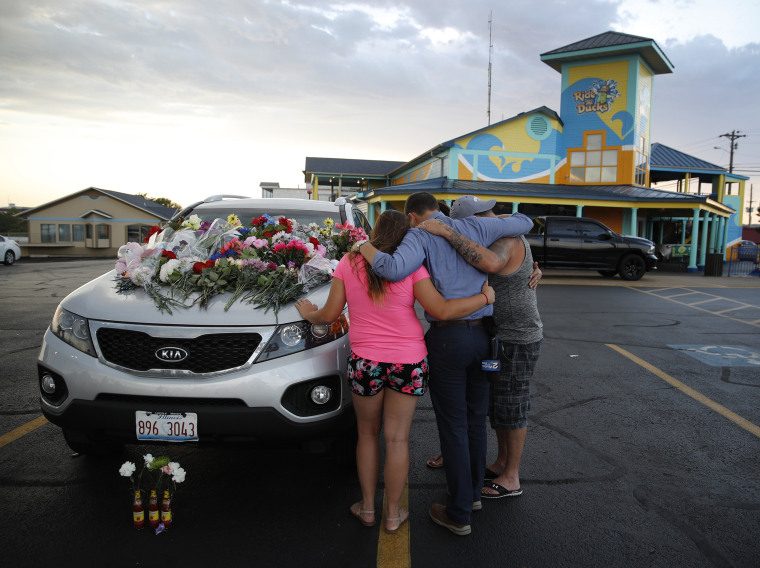 Image: People pray by a car thought to belong to a victim of Thursday's boating accident before a candlelight vigil