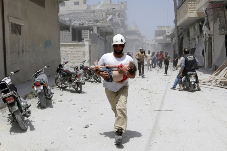 A civil defence member carries injured girl at site hit by airstrikes in rebel-controlled area of Maaret al-Numan town in Idlib province