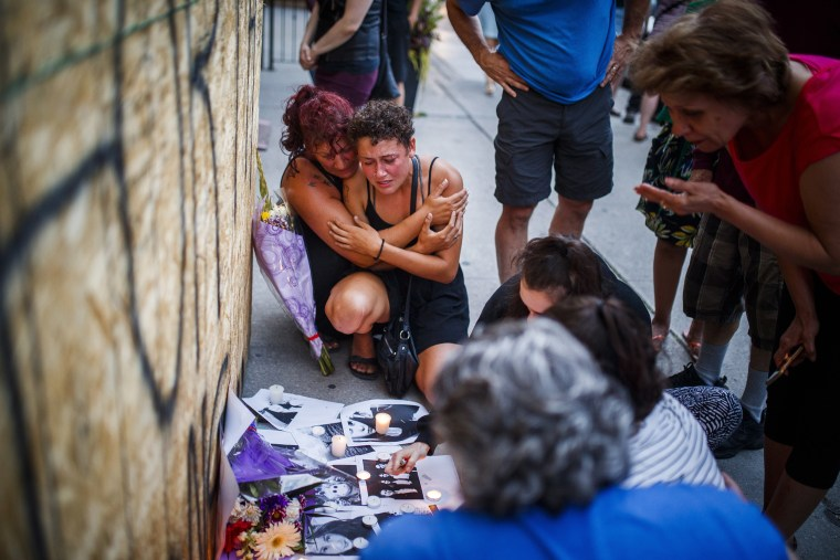 Image: Desirae Shapiro, 19, next to wall kneeling at right, and her mother, Gina Shapiro mourn while visiting a makeshift memorial