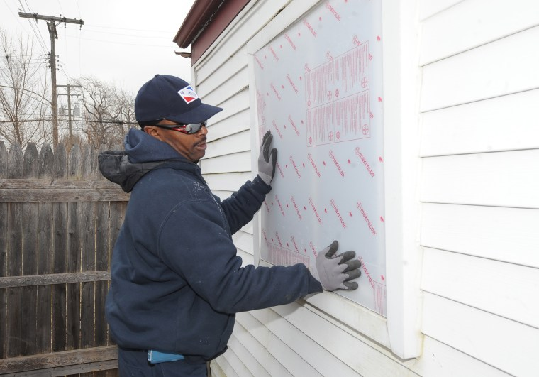 A worker boards a home in Detroit in 2014.