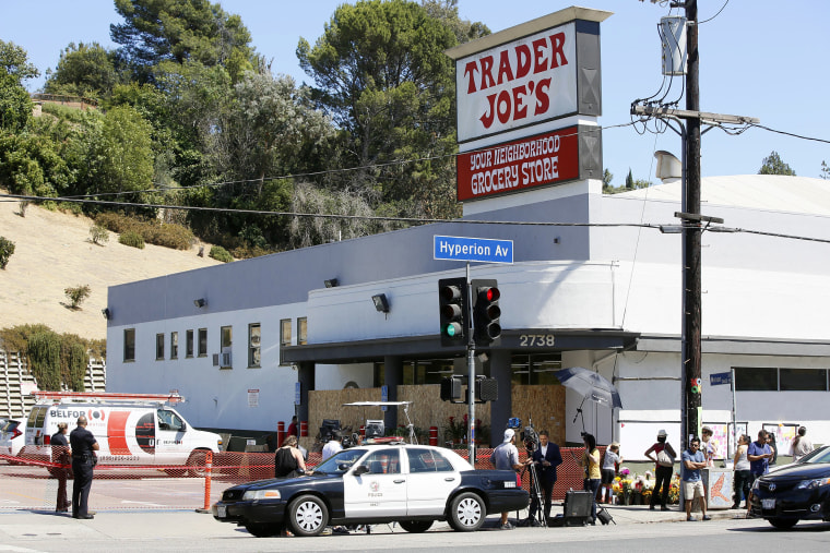 Image: Police officers guard the entrance to the Trader Joe's Los Feliz store, as it remains closed for business