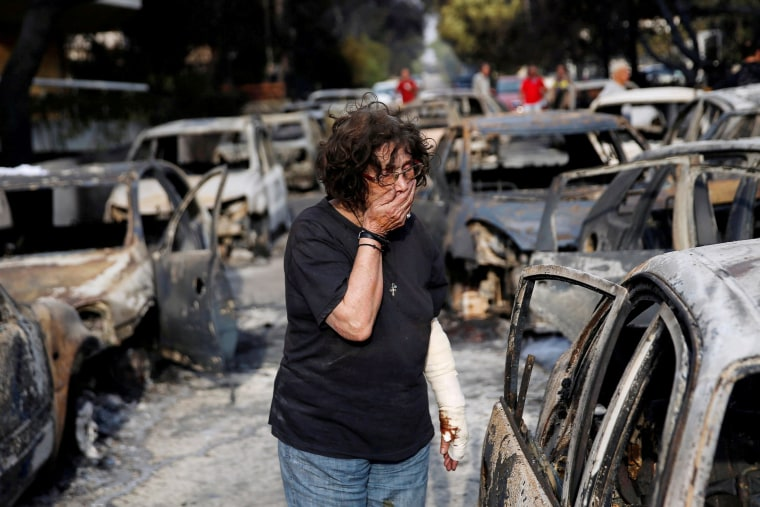Image: A woman reacts as she tries to find her dog, following a wildfire at the village of Mati, near Athens