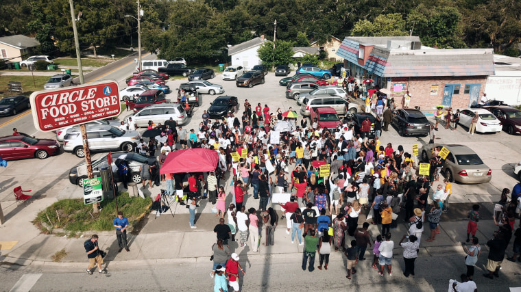 Image: Family, friends and demonstrators gather in a parking lot in Clearwater, Florida