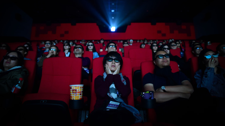 People watch a movie at a theater in Qingdao, China