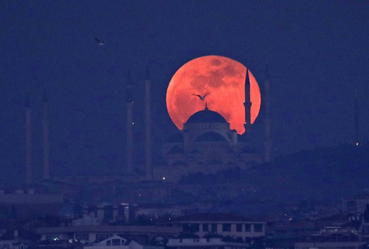 Image: A full moon rises behind a mosque over the Camlica hill in Istanbul