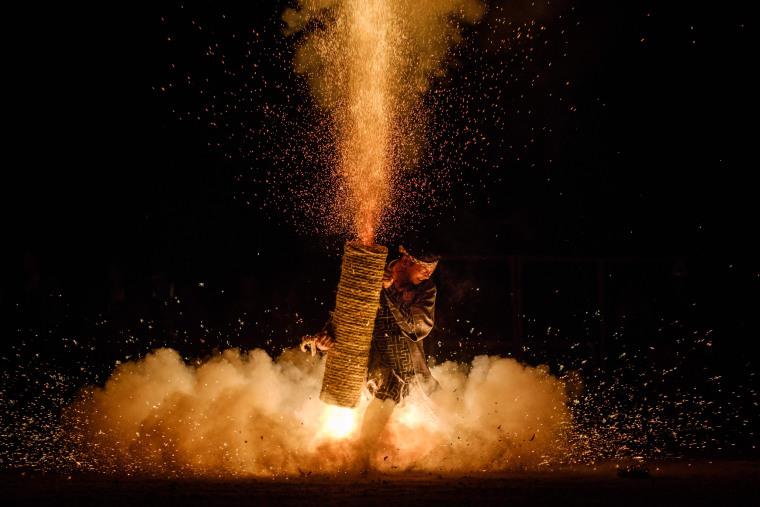 Image: A man holds his handmade Tezutsu hanabi, or handheld firework