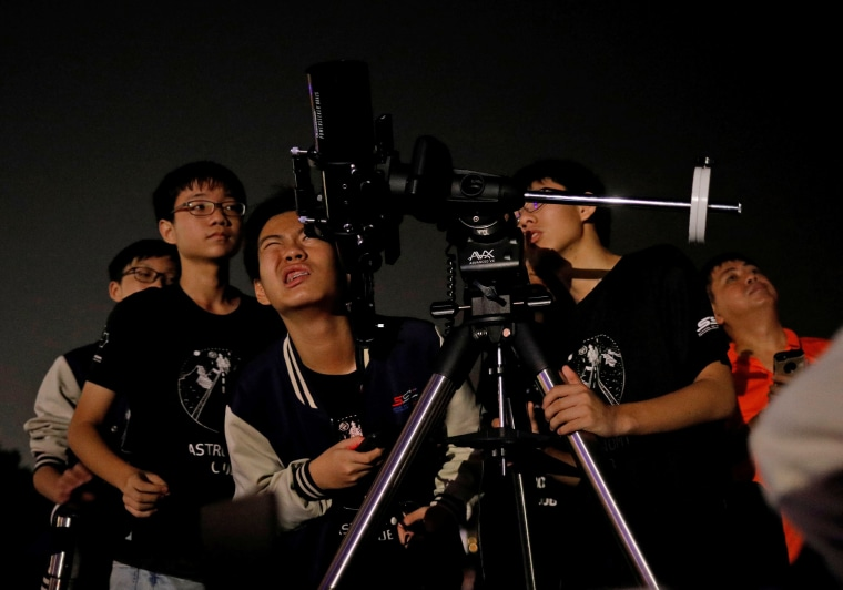 Image: Student astronomy enthusiasts adjust their telescope to see the lunar eclipse of a blood moon at Marina South Pier in Singapore