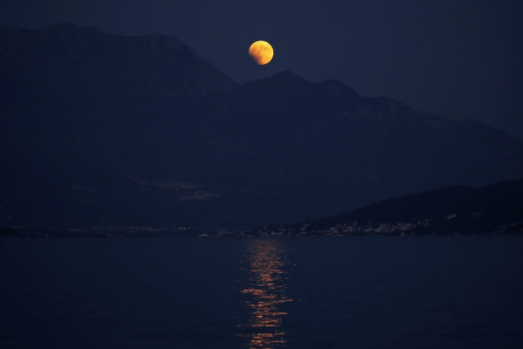 Image: A full moon rising over mountain Lovcen during eclipse is seen from Herceg Nov