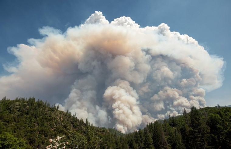 A large pyrocumulus cloud (or cloud of fire) explodes outward during the Carr fire near Redding, California on July 27, 2018. Two firefighters have died and more than 100 homes have burned as wind-whipped flames tore through the region.