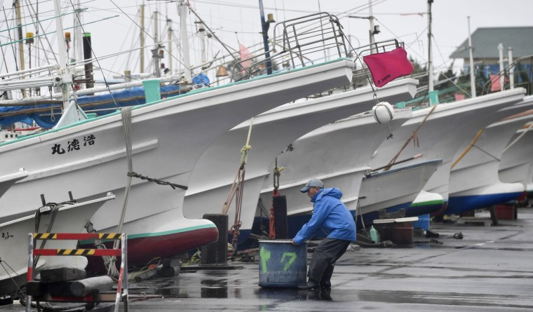 A fisherman looks around fishing boats secured in preparation for an approaching typhoon in Kamogawa, near Tokyo, Saturday, July 28, 2018.