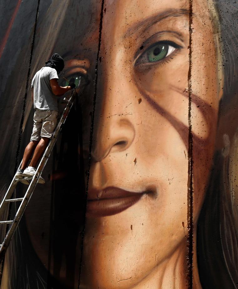 Image: Italian artist Jorit Agoch paints a mural of Ahed Tamim