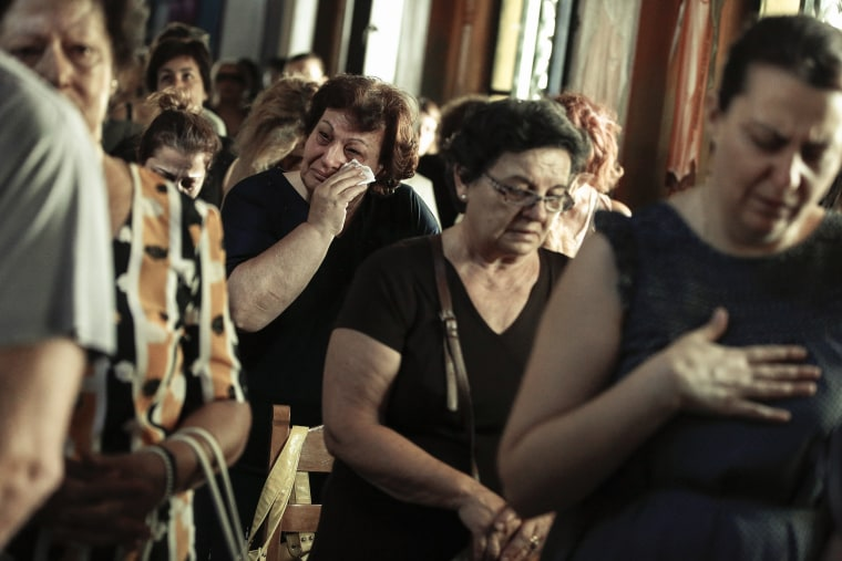Image: Worshipers attend a memorial service for the victims of a forest fire in Mati village, east of Athens