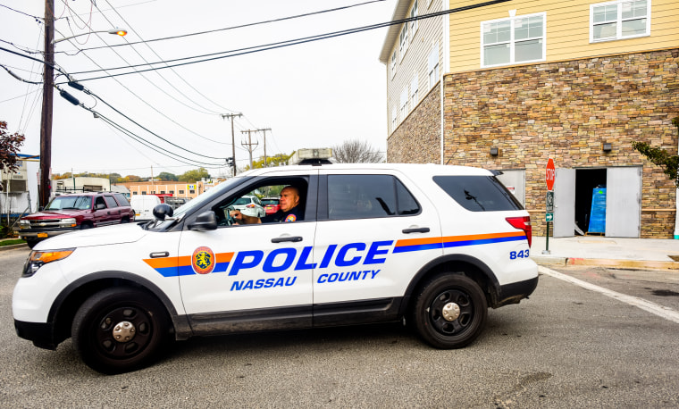A Nassau County Police officer sits in front of a crime scene
