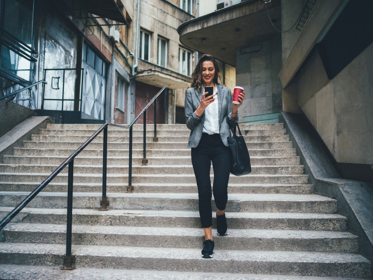 Image: Woman texts and drinks coffee while walking down the stairs