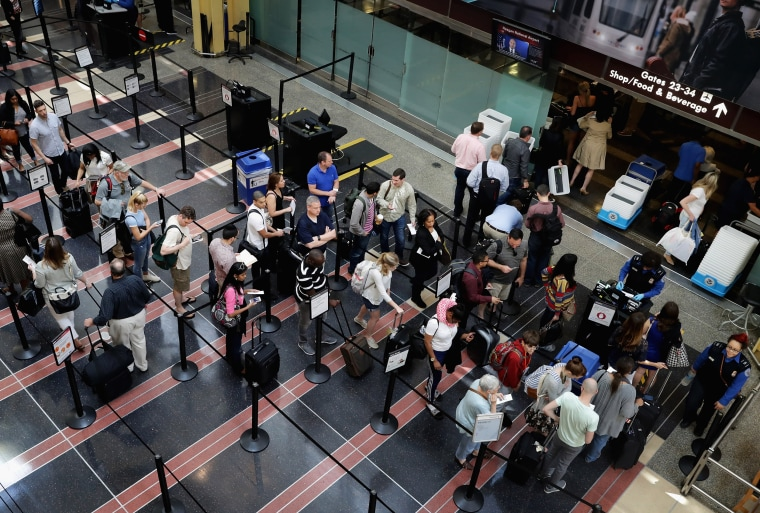 Image: Passengers stand in line outside a Transportation Security Administration checkpoint