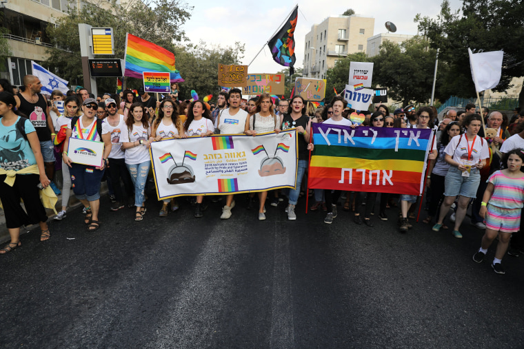 Image: Participants hold banners as they take part in Jerusalem's 17th annual Gay Pride Parade