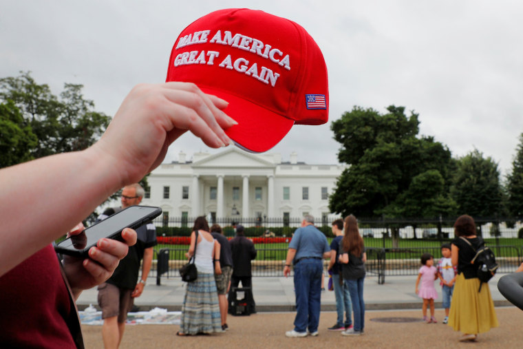 "Image: A tourist holds a ""Make America Great Again"" hat outside the White House in Washington"
