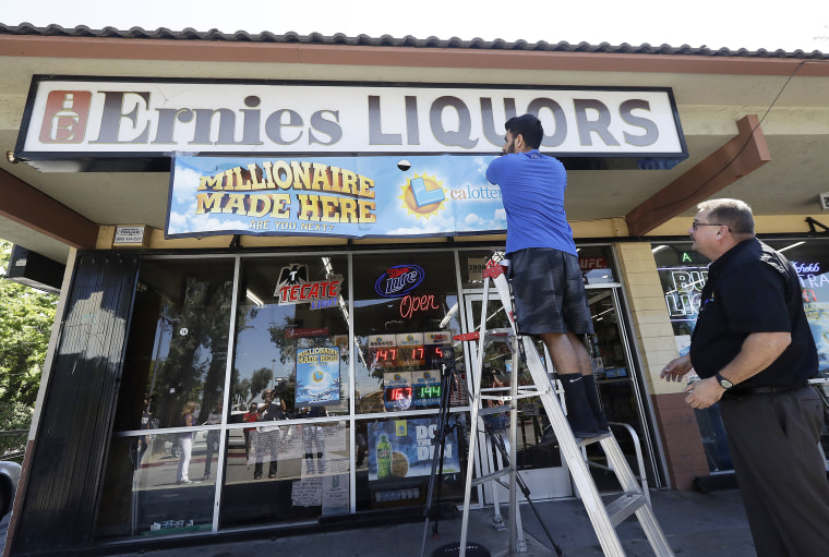 Image: California Lottery official Mike Neis, right, watches as Amol Sachdev hangs a sign over his family's store Ernie's Liquors in San Jose, California on July 25, 2018.