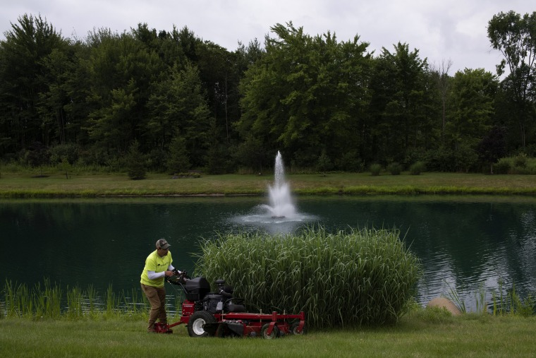 Image: A landscaper mows grass at the Tara At Barrington Estates subdivision