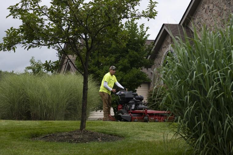 Image: Turfscape Inc. Landscape Technician Alexis Morales mows grass in Aurora, Ohio